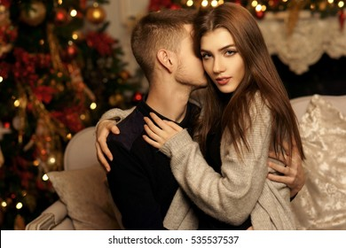 Cute beautiful caucasian young couple sitting at sofa in christmas decorated interior and hugging. Romantic couple staying at home and enjoying tome together