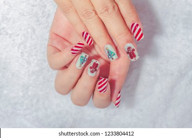 cute beautiful Christmas gel nail art painting lovely brown cookies and pine,fashionista woman doing spa manicure for celebrated holiday party