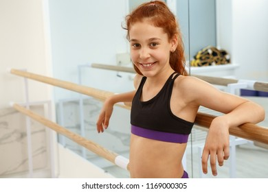 Cute and beautiful girl with ginger hair posing and looking at camera. Positive kid in sportswear smiling and leaning on ballet barres. Slender girl happy after workout and gymnastics.