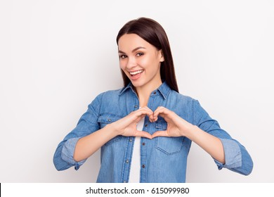 Cute beautiful girl in love making heart with fingers and smiling