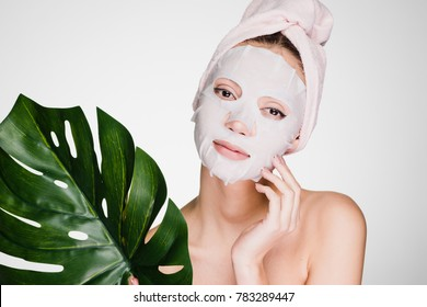 cute beautiful girl with a towel on her head, on her face a tissue mask, holds a green leaf, a spa procedure