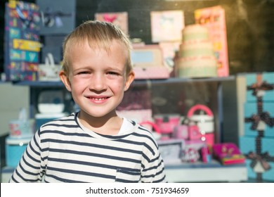 Cute beautiful happy little boy smiling in front of shop-window
