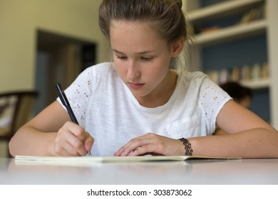 cute beautiful lonely teenager girl studying in the class writing down in her copybook