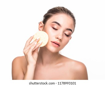 Cute beautiful natural brunette girl cleaning face with cotton sponge smiling looking at camera over white background. Cosmetology and spa.