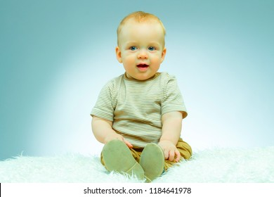 Cute beautiful newborn on a blue background looking at camera and smiling.