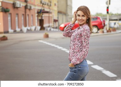 Cute beautiful slim brunette caucasian woman in casual hipster outfit on a walk in european city. Copy space