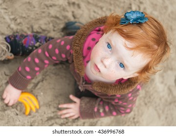 cute beautiful smiling little girl playing at the playground in the park. Happy RED girl climbing on outdoor playground