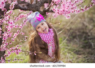 Cute beautiful stylish dressed brunette girl with very long hair standing on a field of spring young peach tree with pink flowers.Lady dressed in rain clothes and blue hat rubber boots spring season.