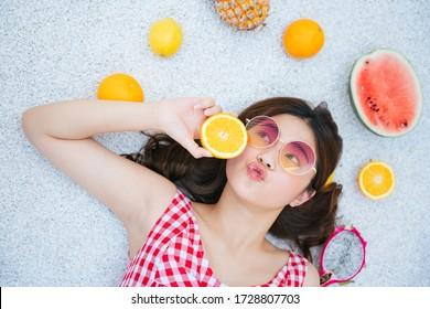 Schöne junge asiatische Frau mit Brillen und rotem Kleid auf dem Boden mit tropischen Früchten. Sommerferien.