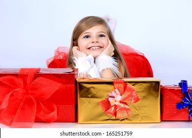 A cute beautiful young girl with long hair in a red dress holding christmas present gift box lying on the floor smiling in studio