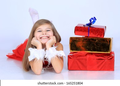 A cute beautiful young girl with long hair in a red dress with christmas present gift box lying on the floor  in studio