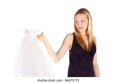 cute beautiful young girl looking at the wedding veil in her hand