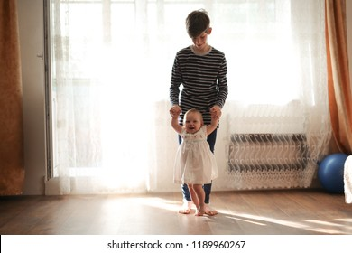 Cute big brother teen help him sister toddler. Happy loving family. Expression and tender, real interior and relationships concept.