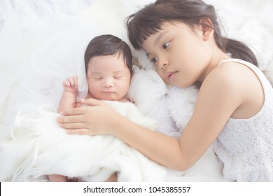 cute big sister with new newborn baby