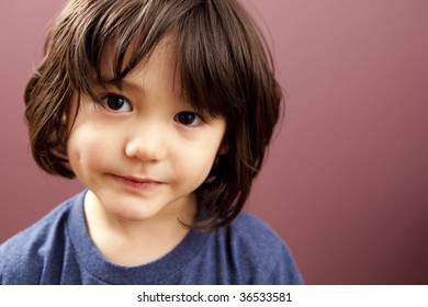 A cute, bi-racial toddler boy is looking off camera.