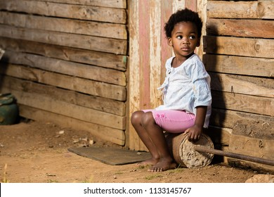 Cute black girl with a serious look on her face while not wearing shoes