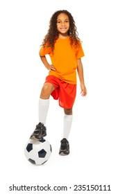 Cute black girl stand on soccer ball in studio