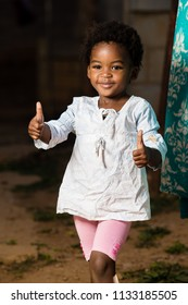 Cute black toddler with a smile on her face while showing thumbs up