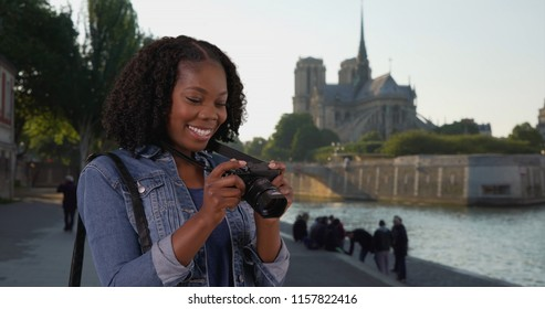 Cute black woman takes photo of Seine river view of Notre Dame in background