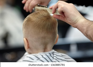Cute blond baby boy in a barber shop having haircut by hairdresser. Hands of stylist with tools. Children's fashion. Indoors, back view, copy space.