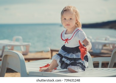 Cute blond baby girl child posing enjoying summer life time on sandy beach sea side on wooden pier with colourful plenty balloons wearing casual dress barefoot.