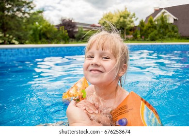 A cute blond baby girl swims at swimming pool with blue colored water outdoors, smiles  and hold parent's hand. Girl wears inflatable sleeves. Concept of parents teaches and takes care of children.