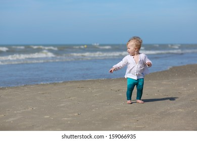 Cute blond baby girl in white blouse is walking along the water on the beach at a North Sea in Belgian coast on a sunny summer day