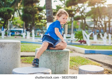 Cute blond boy climbs up the stone blocks on the playground. Childhood, concept.