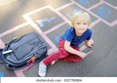 Cute blond boy doing homework sitting on school yard after school with bags laying near. Back to school concept. Little boy on school yard