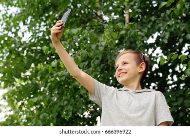 Cute blond boy doing selfie in a park outdoors