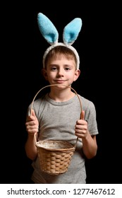 Cute blond boy in hare's ears holding a wicker basket on a black background. Portrait. Vertical frame.