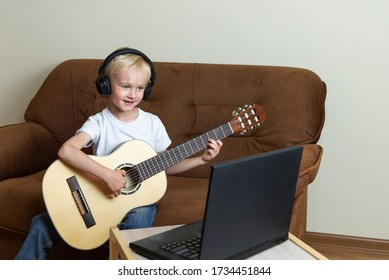 Cute blond boy in headphones plays the guitar and looks at the laptop standing on the table. A fun online lesson on the internet. Digital education. Modern lifestyle in lockdown. Stay at home.