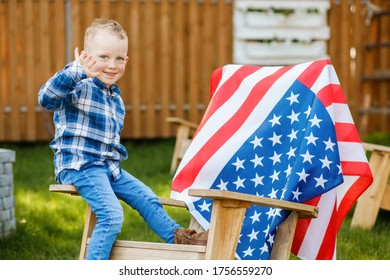 Cute blond boy sitting on a big chair on the background of the American flag. Independence Day