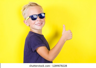 Cute blond boy wearing sunglasses showing Thumbs Up