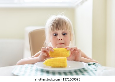 Cute blond caucasian girl holding in hand tasty boiled sweet corn cob and lokking on it with amazed wide opened eyes. Child loves eating  yellow maize. Children summer snack