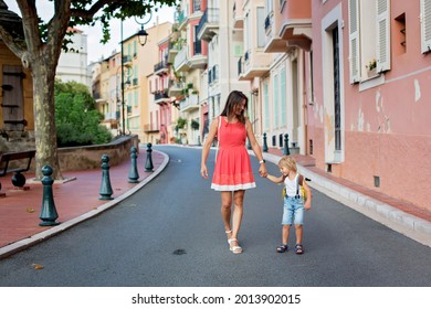 Cute blond child and mom, toddler boy and parent, walking in Monaco ville street, hand in hand summertime