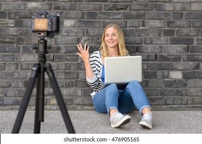 Cute blond female blogger with laptop recording video while sitting and talking with gesturing hands for theme about video blogging