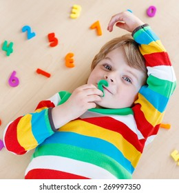 Cute blond funny kid boy playing with lots of colorful plastic digits or numbers, indoor. Child wearing colorful shirt and having fun with learning math
