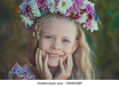 Cute blond girl with blue eyes close portrait wearing wild flowers wreath on top head smiling and looking to camera with eyes full of love joy and life