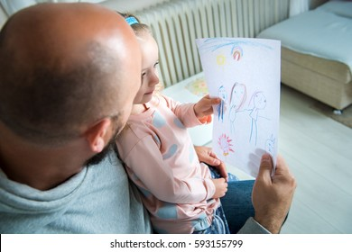 Cute blond girl giving her father a drawing, fathers day concept. Gender stereotyping, gender roles, equality issue. Stay at home dad.