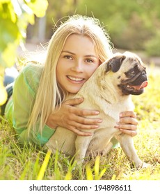 Cute blond girl having fun with her dog at the park