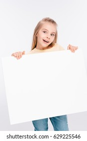 Cute blond girl holding white blank board in hands isolated on white