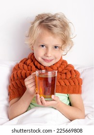 Cute blond girl lying in bed with cup of tea