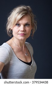 Cute blond girl shot in studio with dark background