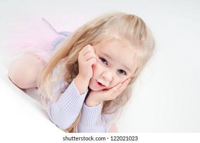 Cute blond girl sitting on the floor