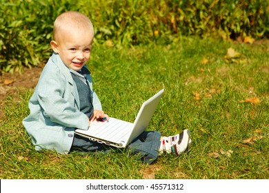 A cute blond kid  sitting on grass with laptop