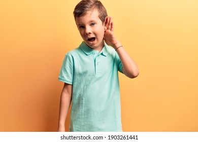 Cute blond kid wearing casual clothes smiling with hand over ear listening and hearing to rumor or gossip. deafness concept.