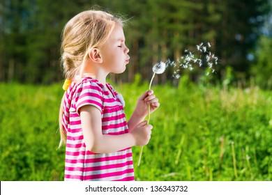 Cute blond little girl blowing a dandelion