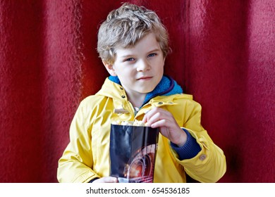 cute blond little kid boy eating popcorn at the cinema before the movie starts. Happy child having fun and waiting for the cartoon or film. Family day, leisure with children