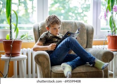 Petit garçon blond mignon lisant un magazine dans une chambre domestique. Un enfant excité lisant à haute voix, assis sur un canapé. Élève, famille, éducation.